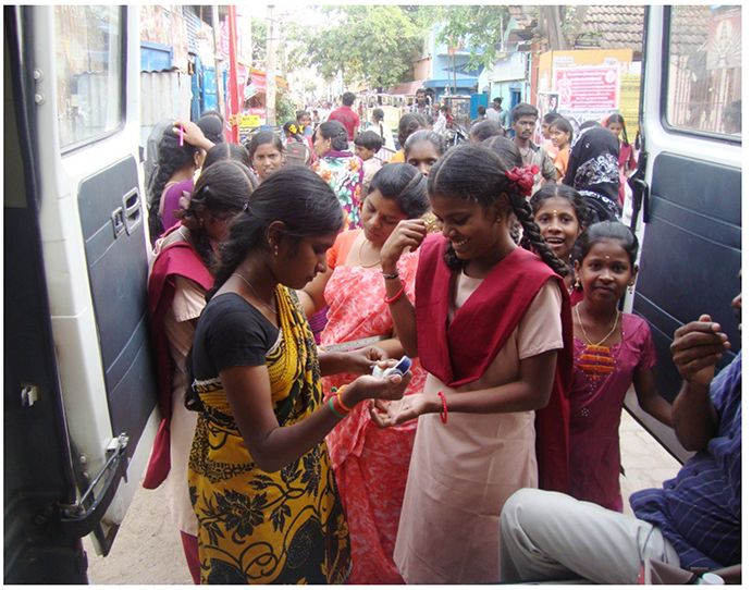 group gathers for anemia tests out of the back of a vehicle