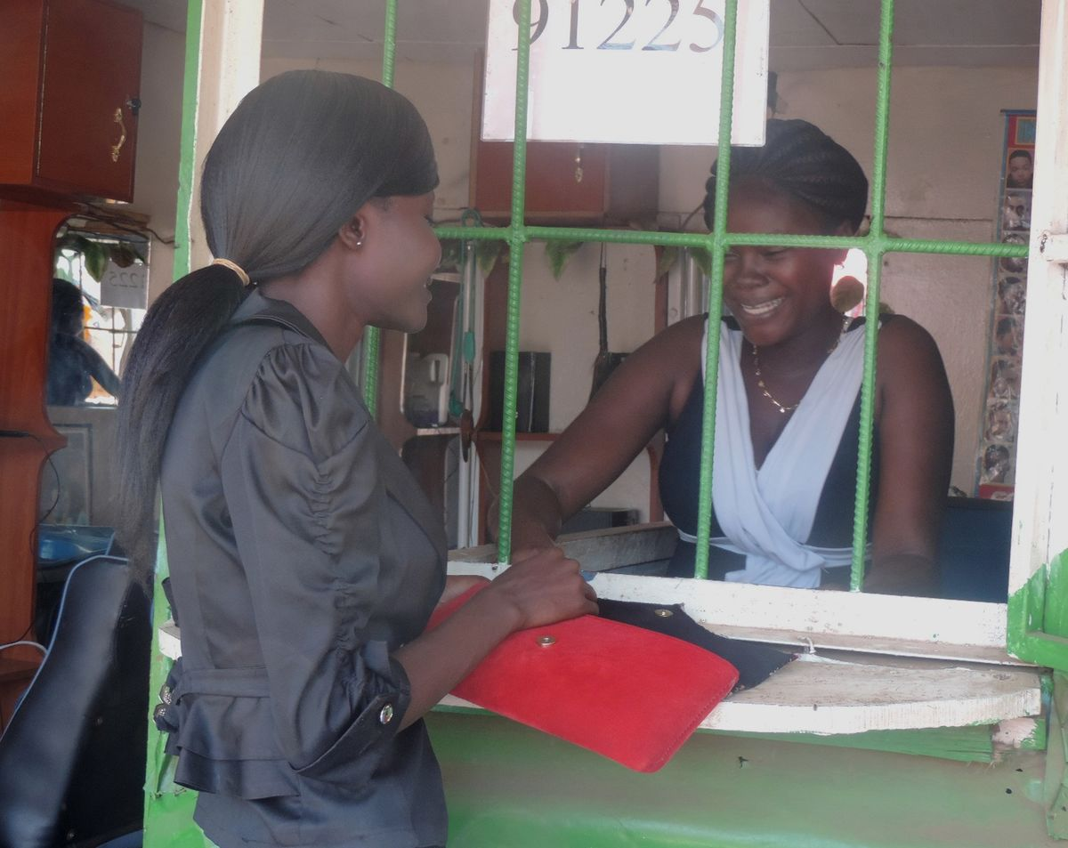 Lillian Akoth at the window of her mobile money transfer service.