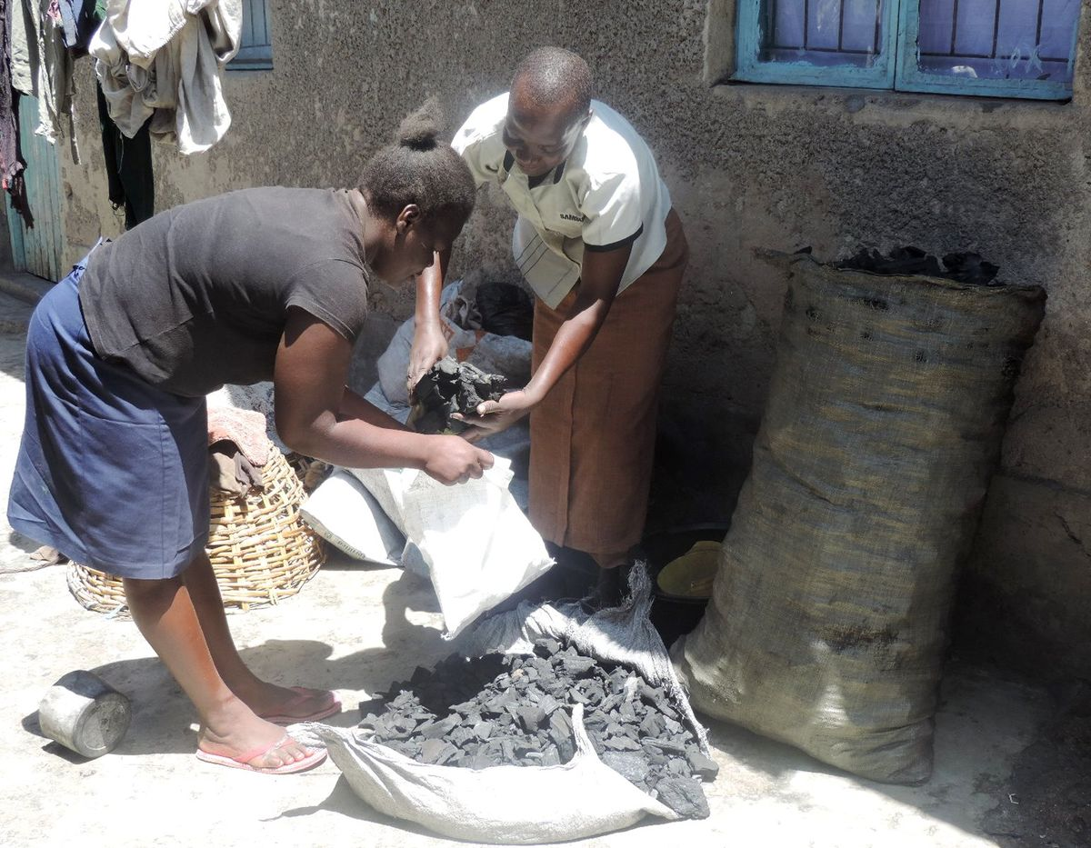 Emmaculate Achieng sells cooking charcoal to a neighbor.