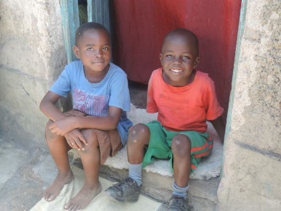 Emmaculate's youngest son and his cousin outside the door to their home.