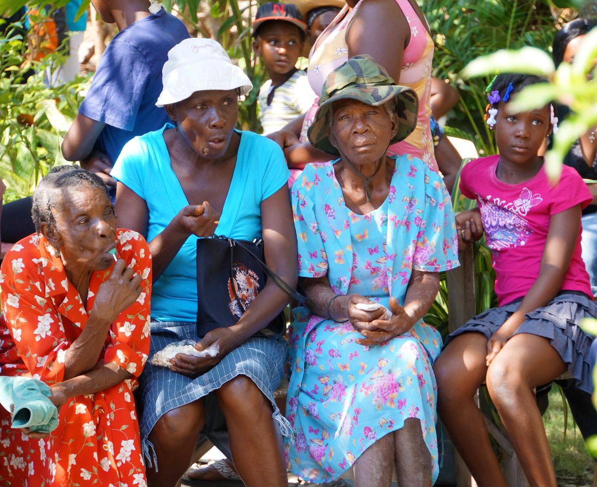 Three older women and a young girl wait for the opening of the mobile women's clinic in Sante Nan Lakou