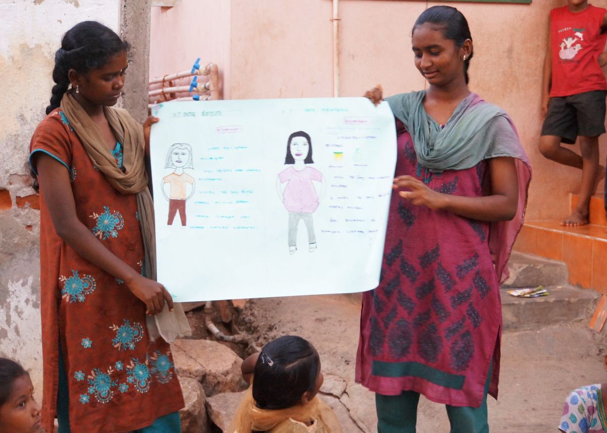 Two women in India teach girls about a new savings program