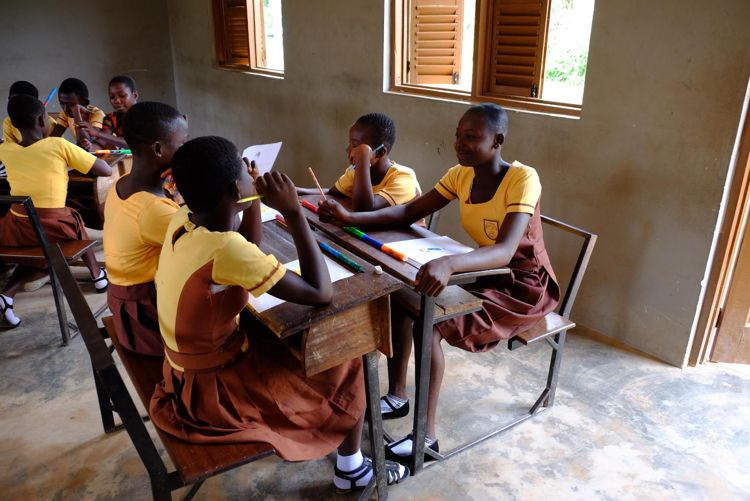 School girls in Ghana gather around a table to work.
