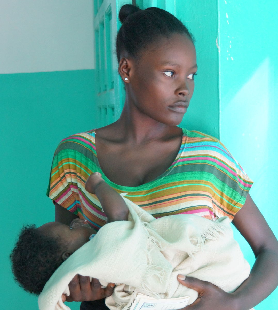 Mother and baby stand outside health clinic