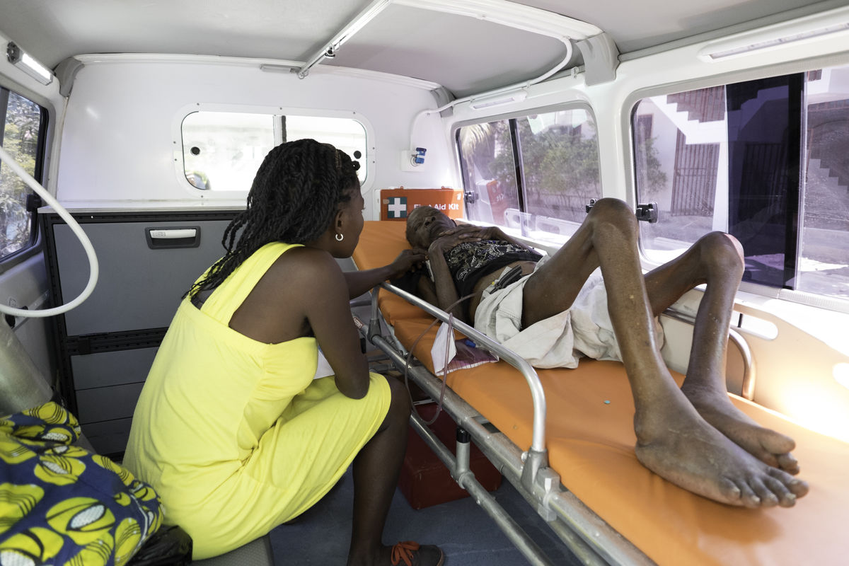 Woman tends to elderly woman in ambulance