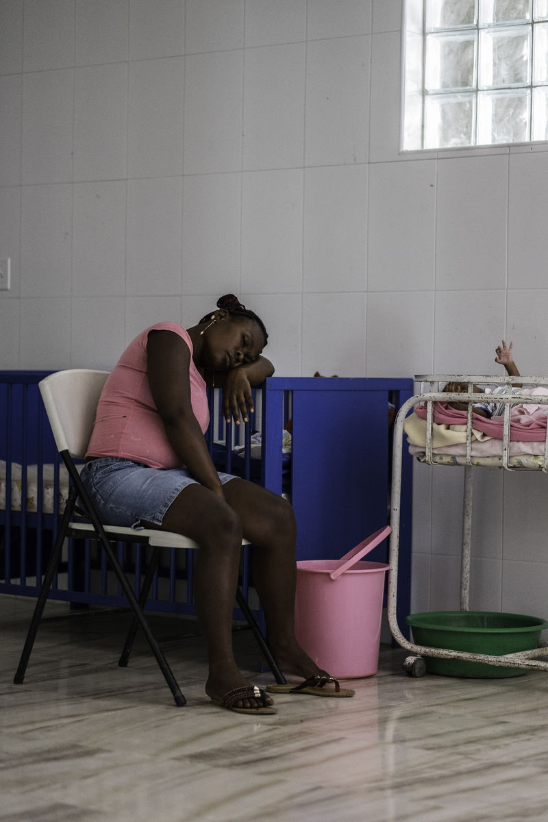 A woman sits exhausted next to her baby at a health clinic.