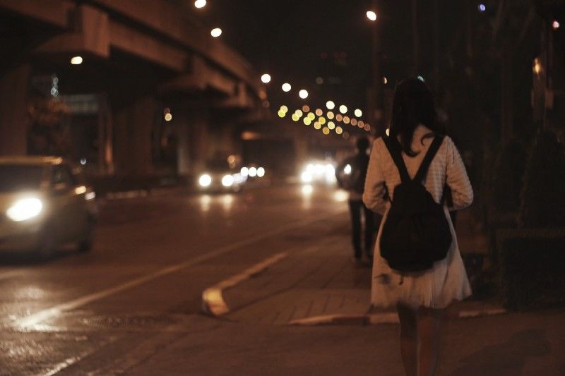 Girl in unsafe city alley.